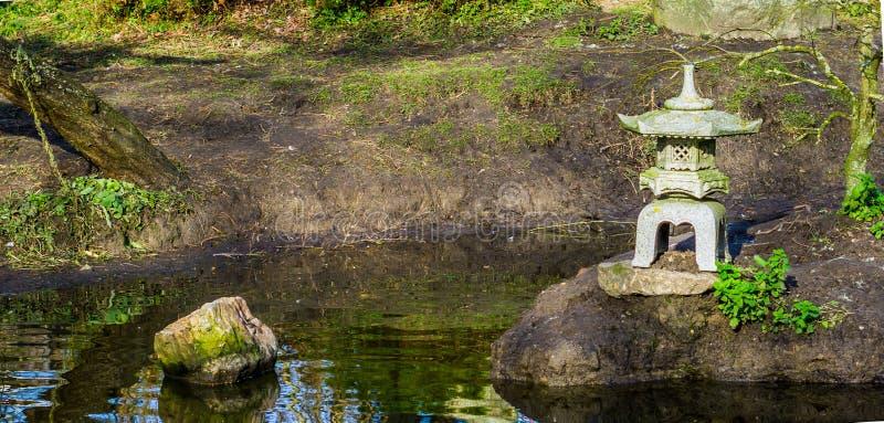 Lagoa de água em um jardim japonês com uma escultura da torre, fundo asiático do jardim imagem de stock