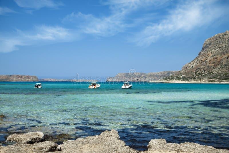 Lagoa de Balos na ilha da Creta em Grécia Barcos de turista na água claro imagem de stock royalty free