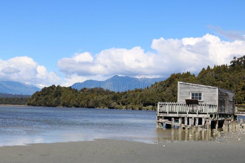 Lagoa de Okarito e construção de madeira nos pernas de pau, NZ imagens de stock