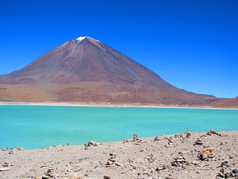 A lagoa e a neve verdes cobriram a montanha fotografia de stock