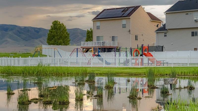 Lagoa gramínea brilhante do panorama com reflexão das casas céu nebuloso e cerca do campo de jogos imagens de stock