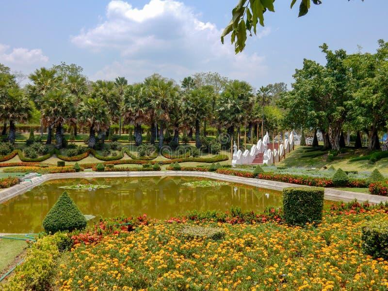 Lagoa no parque cercado por camas de flor com flores e árvores foto de stock royalty free