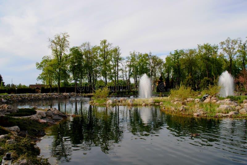Lagoa pequena no parque e na ponte foto de stock
