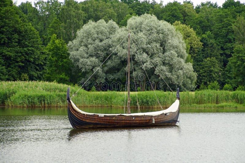 Lagoa selvagem no parque de Nesvizhsky Reconstrução do barco de Viking contra o salgueiro de prata fotografia de stock royalty free