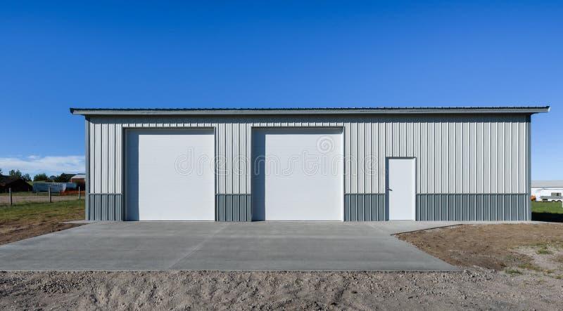 Lagre che sta esclusivamente, garage recentemente costruito nell'area del sobborgo, U.S.A. Grembiule concreto, strada privata immagine stock libera da diritti