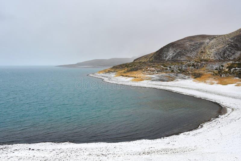 Lagret av den heliga Rakshas Tal sjön i snöfall, västra Tibet, Kina Denna sjö också som är bekant som demon sjön, Ravana Tal elle royaltyfri fotografi