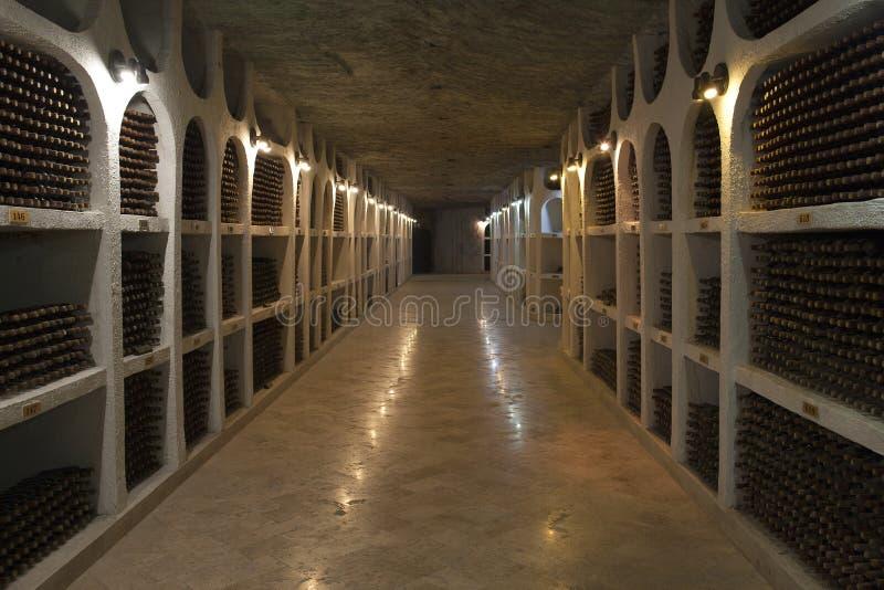 Lagringen av vinflaskor i en vinkällare arkivfoto