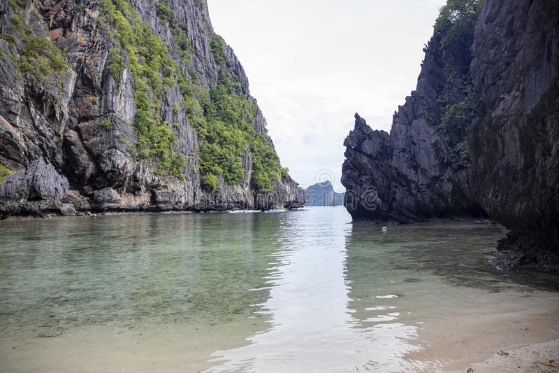 Lagun för blått vatten av den tropiska ön med vaggar bildande och sandstranden Pittoresk lagun för vulkanisk ö royaltyfri foto