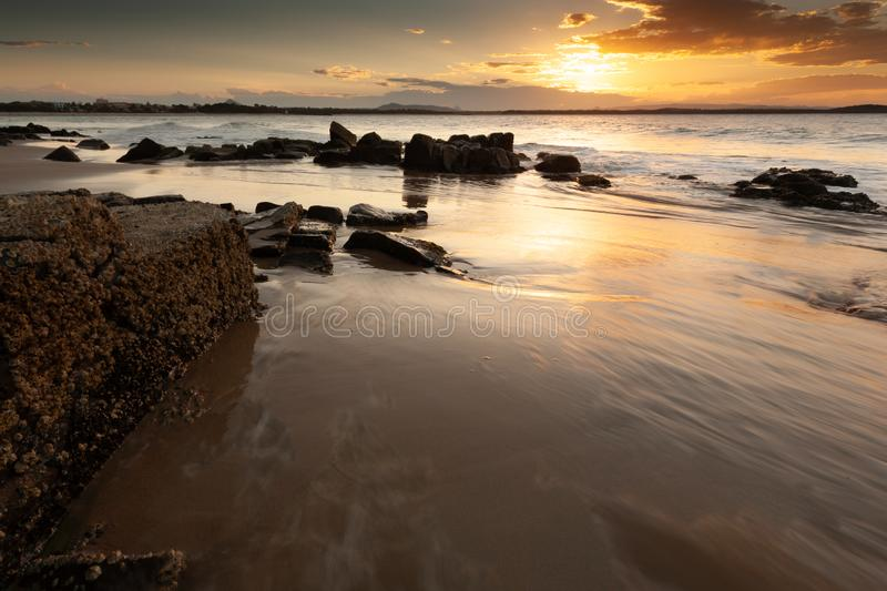 Laguna Bay, Noosa Heads, Sunshine Coast, Queensland, Australia. Sunset with wet sand and rocks in foreground, at Laguna Bay, Noosa Heads, Sunshine Coast stock photo
