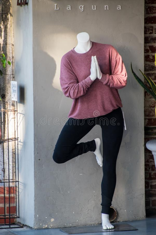 Headless praying mannequin wearing a pink shirt and black leggings royalty free stock photography