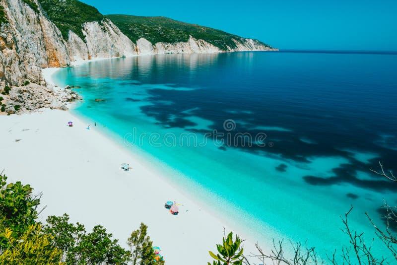 Laguna de la playa de Sunny Fteri con la costa costa rocosa, Kefalonia, Grecia Los turistas bajo frialdad del paraguas se relajan fotos de archivo