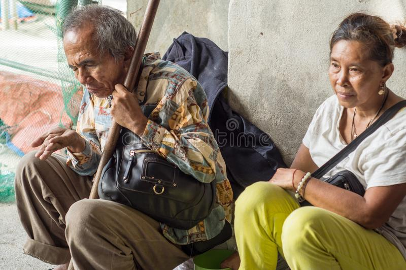 Blind old male beggar and woman escort seeking alms at church portal ruins. stock photos