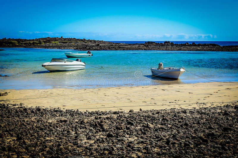 Laguna with white boats at Isla de los Lobos. A turquoise bay at Isla de los Lobos, situated North-East of Fuerteventura, Canary Islands, Spain royalty free stock photos