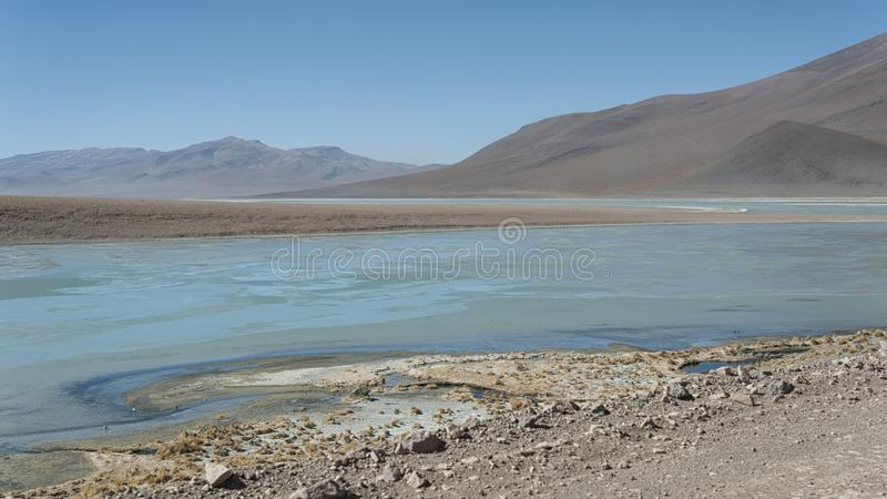 Laguna y Termas de Polques hot spring pool with Salar de Chalviri in background, Salar de Uyuni, Potosi, Bolivia. South America royalty free stock photo