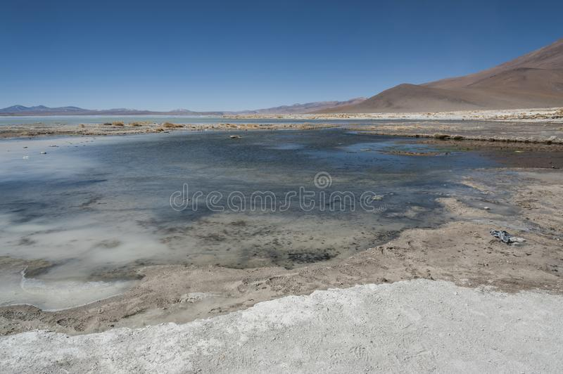 Laguna y Termas de Polques hot spring pool with Salar de Chalviri in background, Salar de Uyuni, Potosi, Bolivia royalty free stock photos