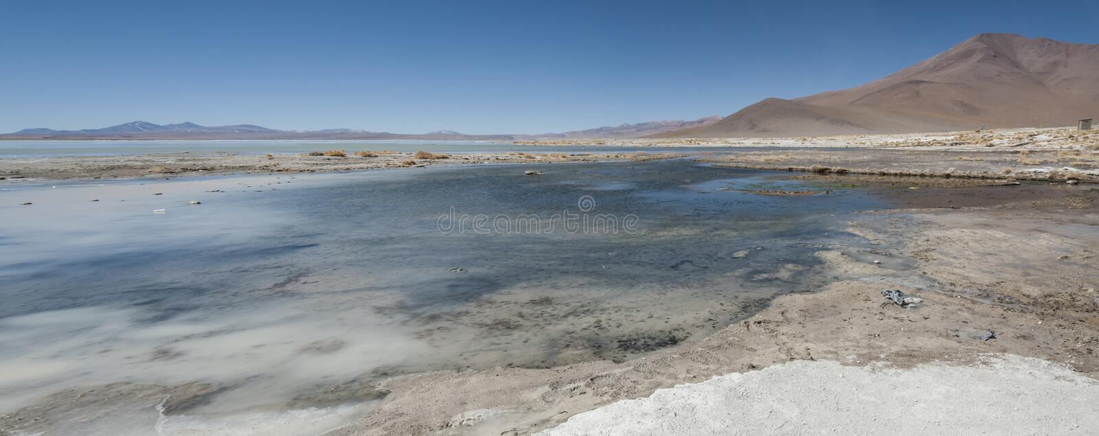 Laguna y Termas de Polques hot spring pool with Salar de Chalviri in background, Salar de Uyuni, Potosi, Bolivia royalty free stock photo