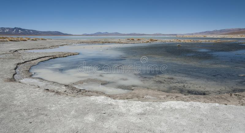 Laguna y Termas de Polques hot spring pool with Salar de Chalviri in background, Salar de Uyuni, Potosi, Bolivia stock photo