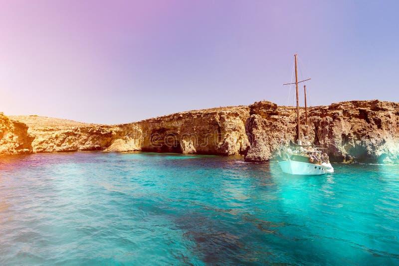 Lagune bleue de Malte et eau et bateau montagneux de beauté de côte image stock