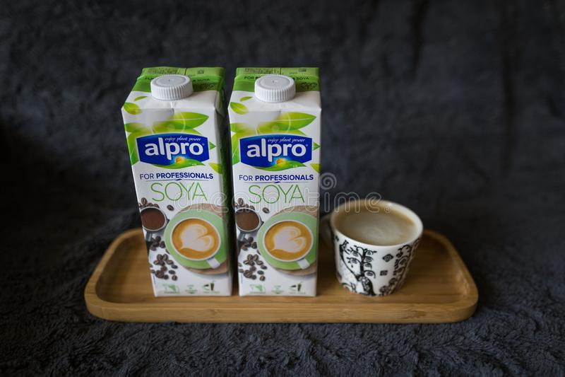 LAHTI, FINLANDIA - 24 DE JULHO DE 2019: Duas caixas do leite de soja por Alpro e uma xícara de café em uma bandeja de madeira fotos de stock royalty free