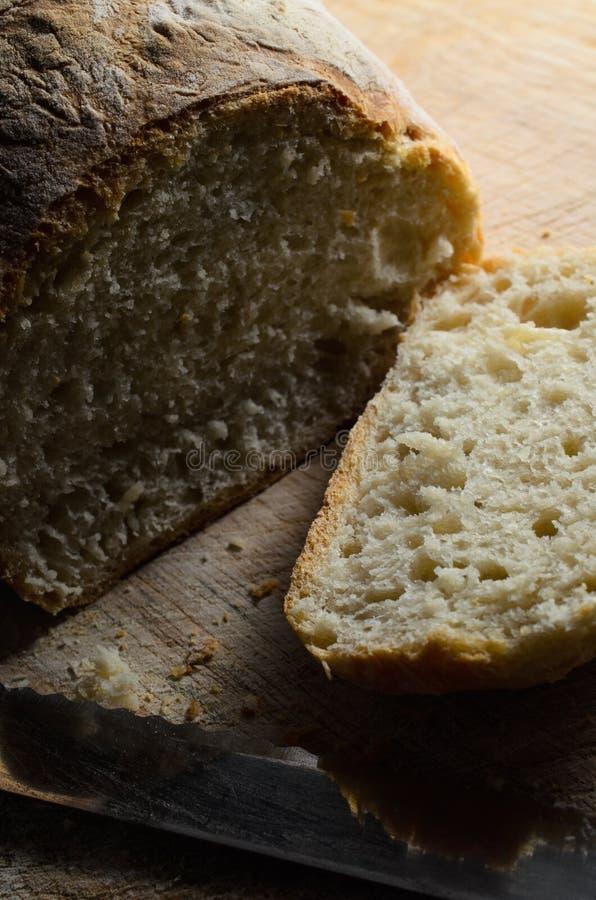 Laib des frisch gebackenen Brotes mit geschnittenem Sluce lizenzfreie stockbilder