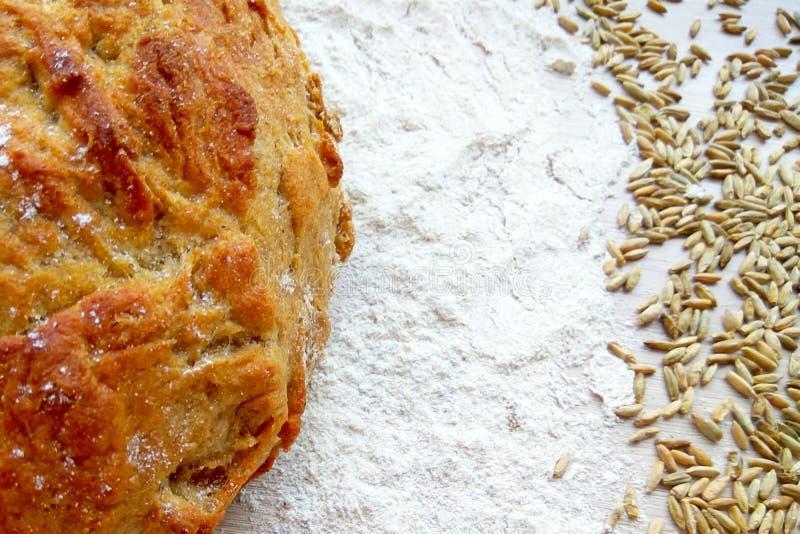 Laib des frischen gebackenen Weizen- und Roggenbrotes mit Körnern und Weißmehl auf Holztischhintergrund stockfoto