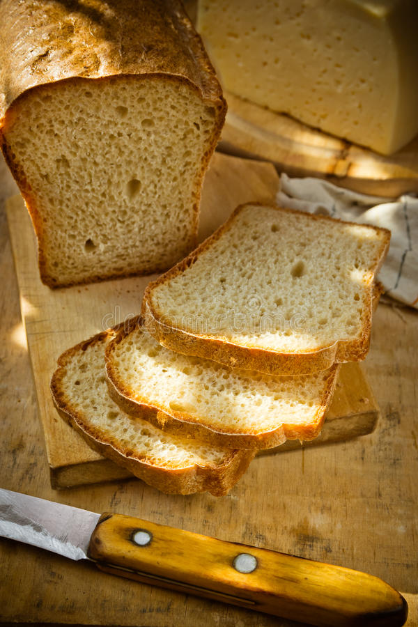 Laib des Sauerteigvollweizenbrotes schnitt in Scheiben, goldene Kruste, Klumpen des Käses, Leinentuch, hölzerner Küchentisch lizenzfreie stockfotos