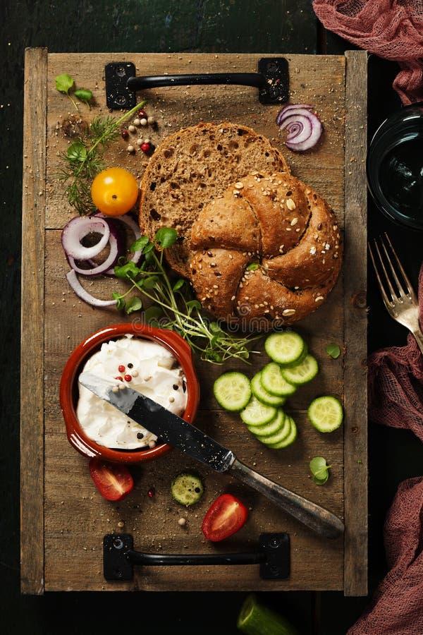 Laib des selbst gemachten Brotes und frische Bestandteile für die Herstellung des Vegetariers stockbild