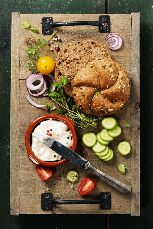 Laib des selbst gemachten Brotes und frische Bestandteile für die Herstellung des Vegetariers stockfoto