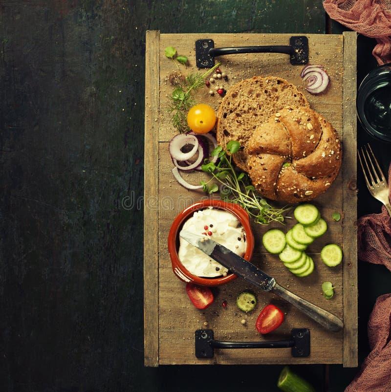 Laib des selbst gemachten Brotes und frische Bestandteile für die Herstellung des Vegetariers stockbilder