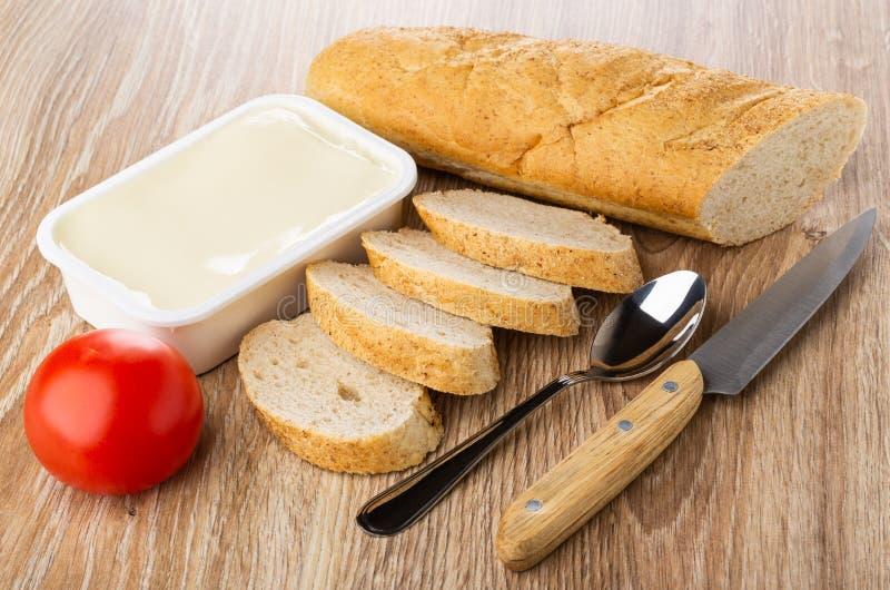 Laib und Stücke Brot, Plastikglas mit geschmolzenem Käse, Tomate, Löffel, Messer auf Holztisch lizenzfreie stockfotografie