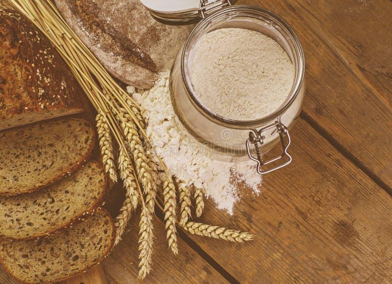 Laibe des Brotes, Scheiben brot, Weizenmehl und Ohren des Kornes auf hölzernem Hintergrund Rustikales und ländliches Konzept Absc lizenzfreie stockfotografie