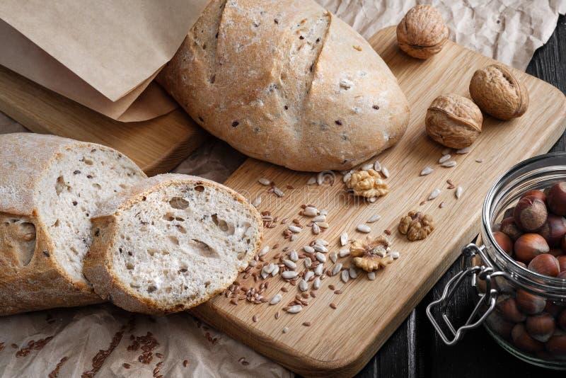 Laibe des grauen Brotes mit Samen, in einer Papiertüte, liegen auf einer schwarzen Tabelle, die vom Holz gemacht wird lizenzfreies stockfoto