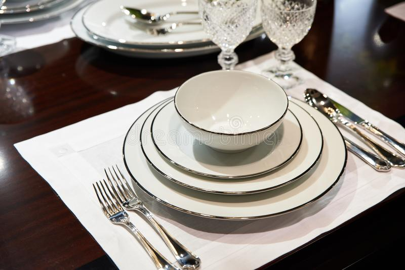 Table served with expensive white dishes and crystal glasses stock photos