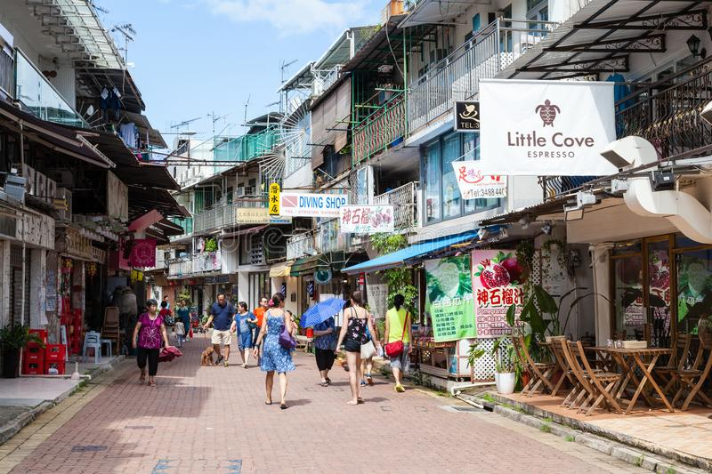 Laidback Community in Sai Kung Village, Hong Kong. HONG KONG - JULY 14, 2014: Tourists and locals stroll along Sai Kung`s old neighborhood on See Cheung Street stock image