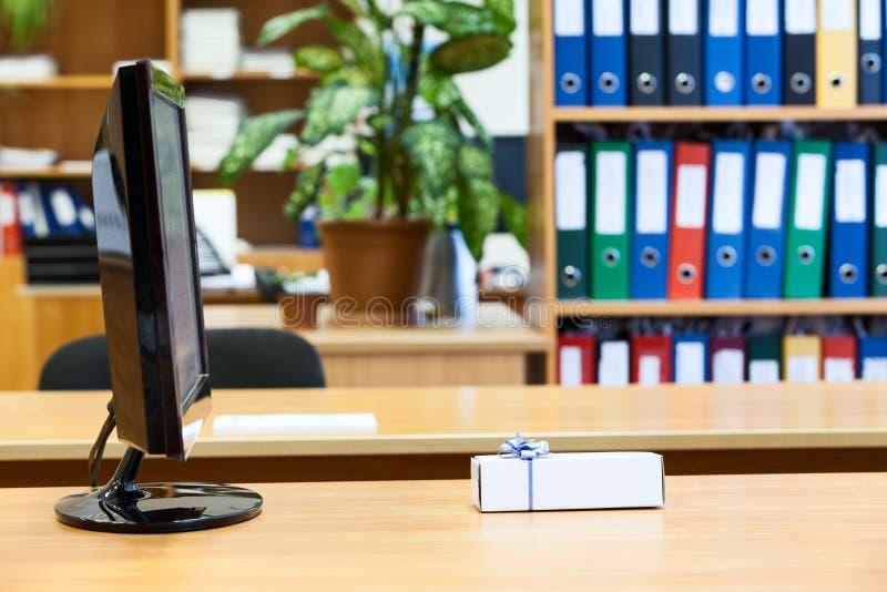 laing在显示器屏幕前面的小礼物盒 库存照片