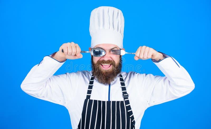 Laisse le plat d'essai Chef affamé prêt à essayer la nourriture Heure d'essayer le goût Cuillère et fourchette de sourire heureus photo stock
