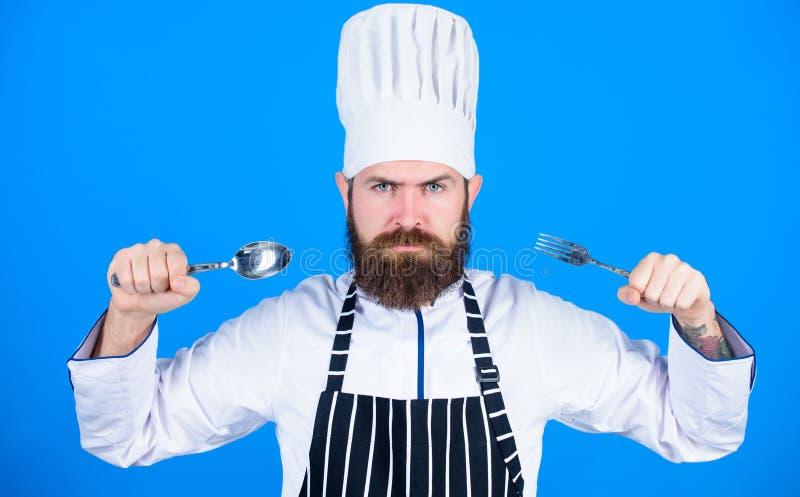 Laisse le plat d'essai Chef affamé prêt à essayer la nourriture Heure d'essayer le goût Cuillère et fourchette strictes sérieuses images libres de droits