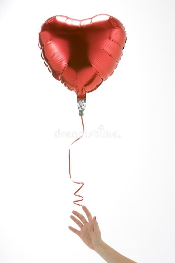 Laisser de main vont du ballon en forme de coeur images stock