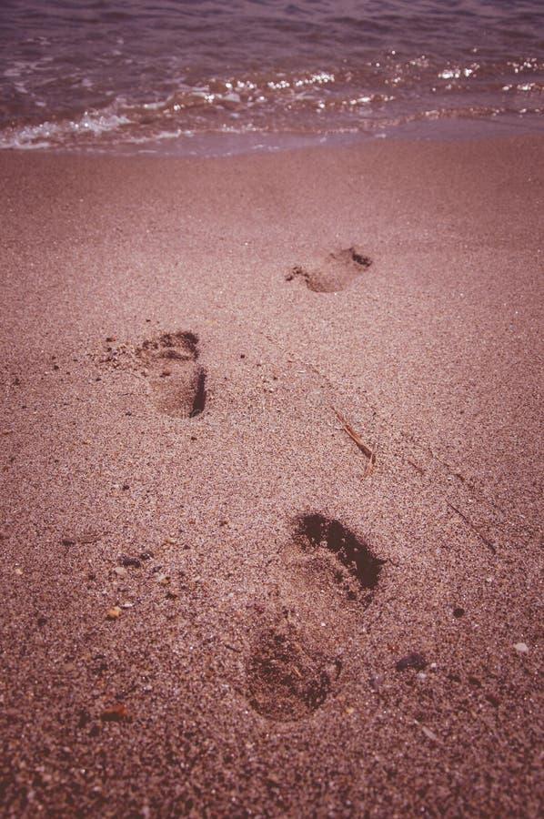 Laisser des empreintes de pas dans le sable en mer images stock
