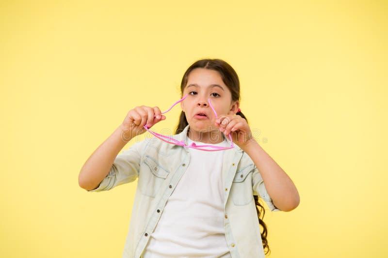 Laissez-moi voir La fille d'enfant met les lunettes en forme de coeur Visage sérieux de fille mettant des verres dessus Lunettes  photos libres de droits