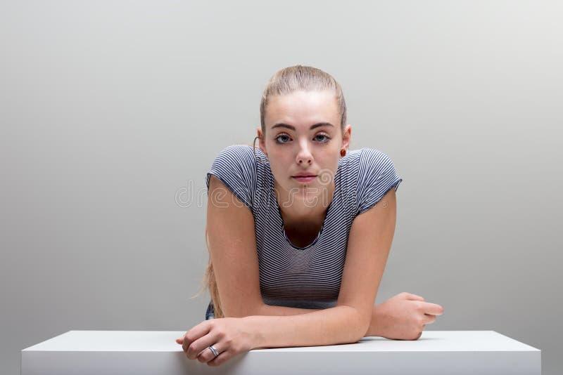 Laissez vers le bas le portrait de femme sur le gris photo stock