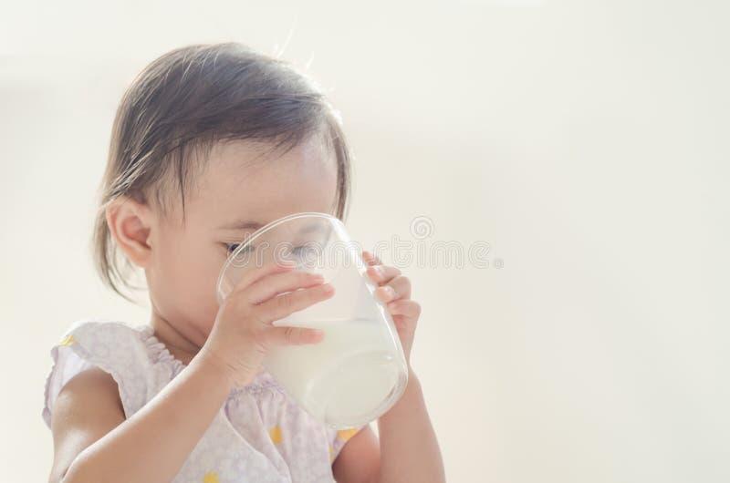 Lait boisson asiatique mignon de fille d'enfant en bas âge de grand verre sur le Ba blanc images stock