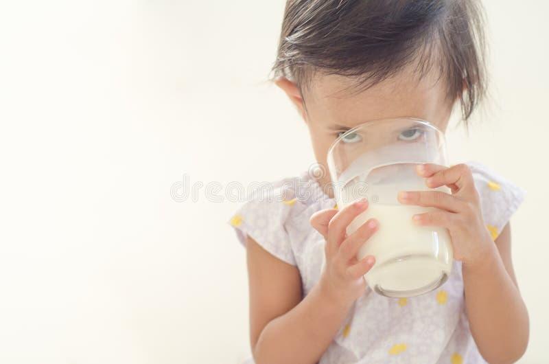 Lait boisson asiatique mignon de fille d'enfant en bas âge de grand verre sur le Ba blanc photos libres de droits