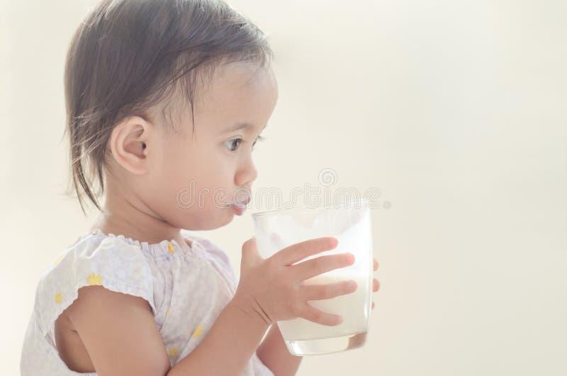 Lait boisson asiatique mignon de fille d'enfant en bas âge de grand verre sur le Ba blanc images libres de droits