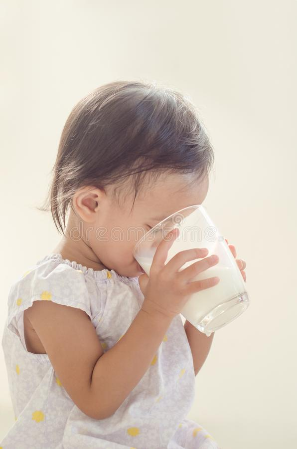 Lait boisson asiatique mignon de fille d'enfant en bas âge de grand verre sur le Ba blanc image stock