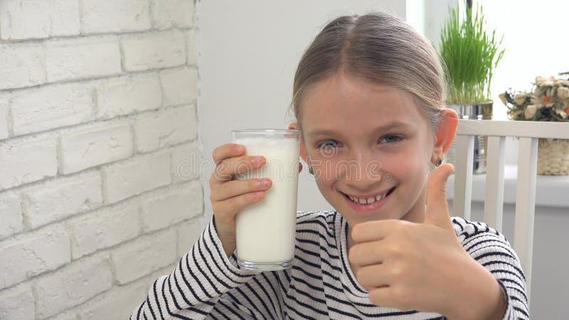 Lait boisson d'enfant au petit déjeuner dans la cuisine, fille goûtant des laitages photographie stock libre de droits