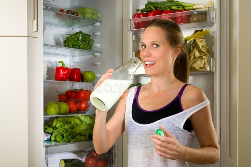Lait boisson sportif de femme pour la nutrition saine dans la cuisine image stock
