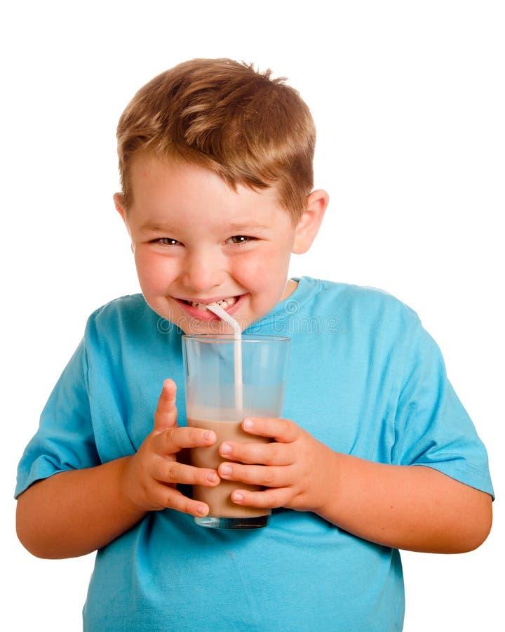 Lait chocolaté potable de sourire heureux d'enfant image stock