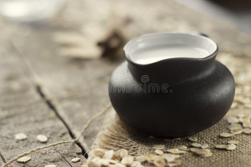 Lait d'avoine dans un pot sur le fond du sac et du bois Lait blanc Lait de Vegan images stock