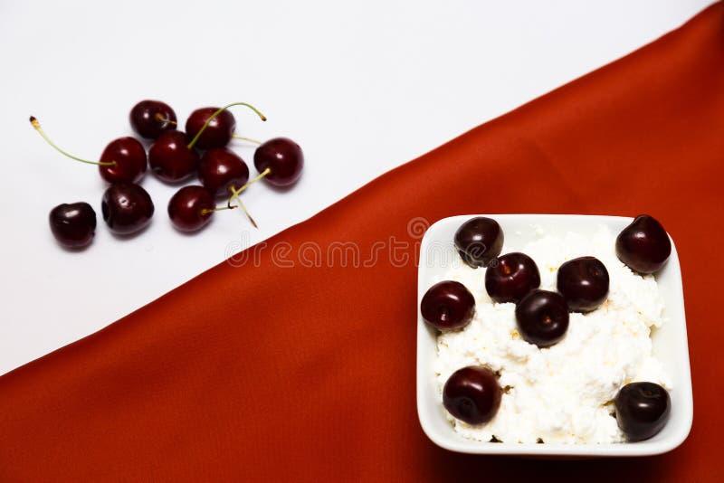 Lait dans un fromage blanc de bouteille et des baies de cerise sur un fond rouge et blanc photo libre de droits